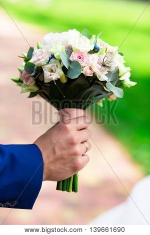 Live white butterfly on wedding bouquet in summer