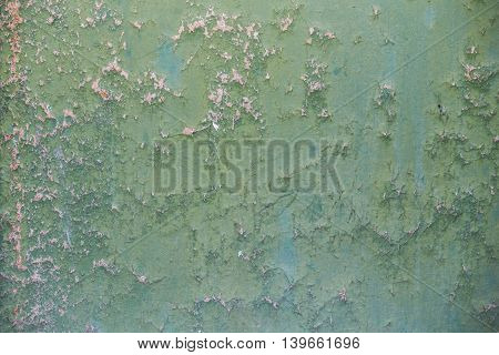 The texture of wall with cracks and green paint.
