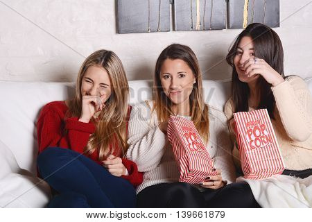 Portrait of three and beautiful young friends eating popcorn and watching movies. Indoors.