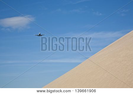 gravel pit hill with approaching aircraft under blue sky