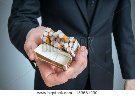 Man Is Offering Cigarette From Cigarette Pack.