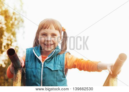 Portrait of a young girl on the uneven bars in autumn day.
