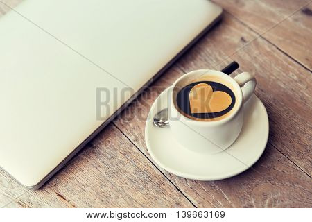 technology, business, valentines day and love concept- close up of open laptop computer and coffee cup with heart shape symbol on surface on table at office or hotel room