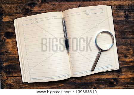 Business appointments agenda notebook with pencil and loupe on office desk top view with blank pages as copy space