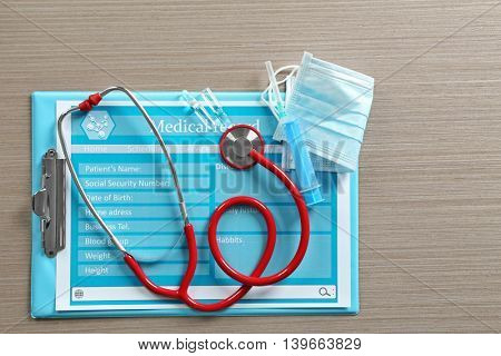 Red stethoscope with medical record on wooden table