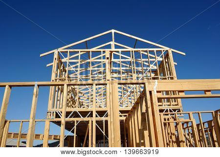 Timber frame of house under construction over blue sky