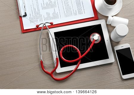 Red stethoscope with tablet and accessories on wooden table
