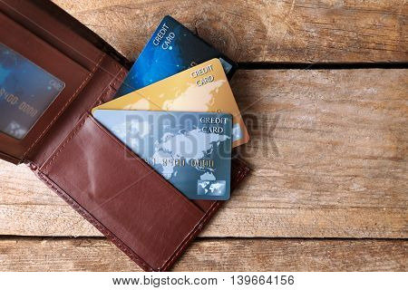 Credit cards in leather wallet on wooden background