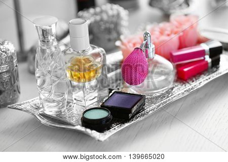 Old silver tray with cosmetics on light dressing table