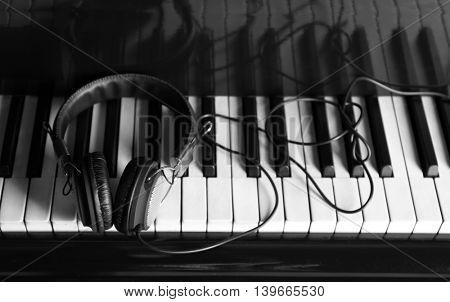 Modern headphones on piano keys