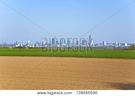 Freshly Ploughed Field With Cityscape Of Frankfurt At The Horizon