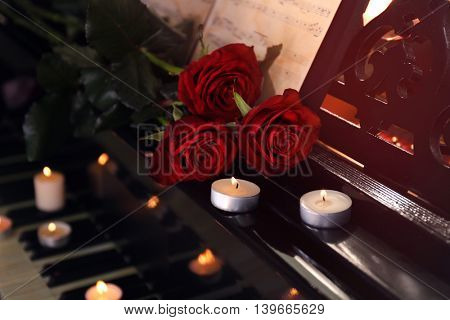 Piano with candles, roses and music notes