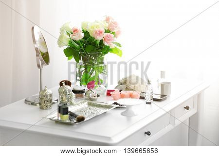 Bouquet of roses and cosmetic set on light dressing table