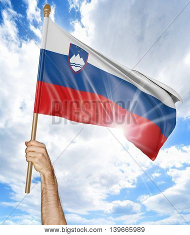Person's hand holding the Slovenian national flag and waving it in the sky, 3D rendering
