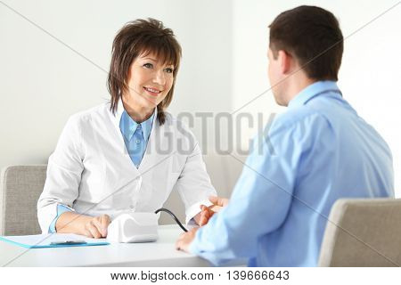 Female doctor measuring man blood pressure in clinic