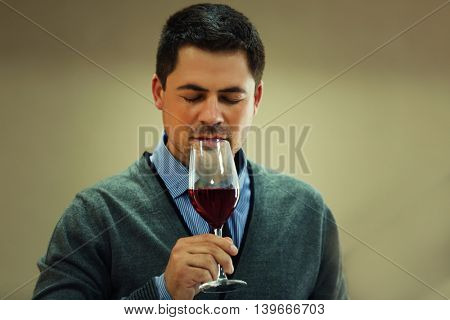 Handsome man tasting red wine