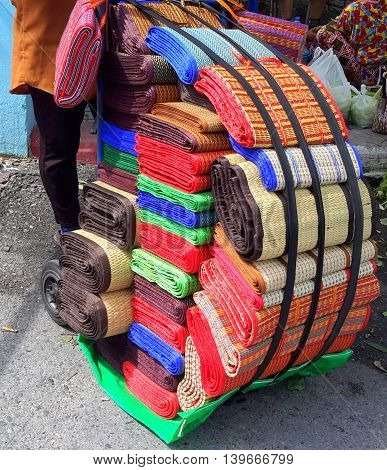 vendor pushing dolly loaded with stacks of rolled colorful woven handmade and factory-made picnic mats, Songkhla, Thailand