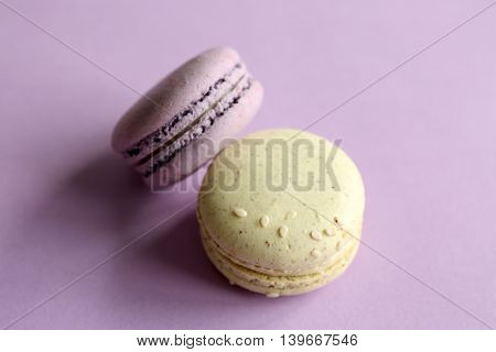 Colorful tasty macaroons on purple background