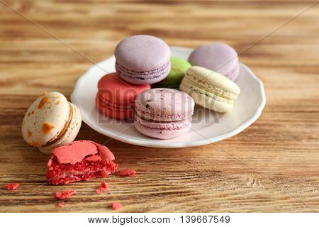 Colorful tasty macaroons in plate on wooden background