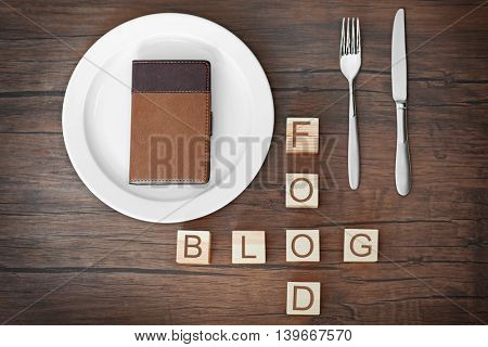 Wooden cubes with words FOOD BLOG and notebook on plate