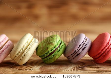 Colorful tasty macaroons on wooden background