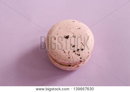 Tasty macaroon on purple background