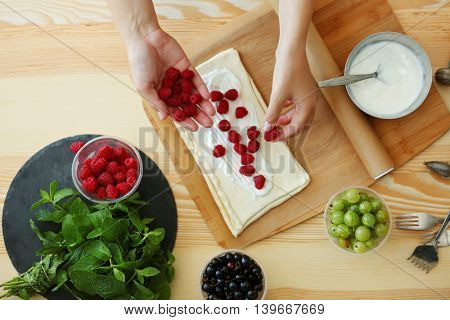 Woman making berry dessert, top view