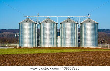 silver silo in rural landscape under blue sky