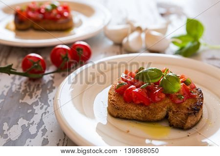 Closeup of Italian bruschetta with tomato and basil over an old table