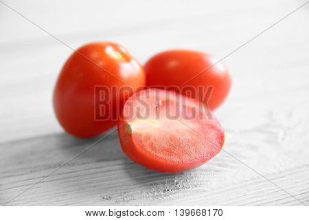Red juicy tomatoes and slice on light wooden background