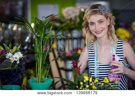 Female florist holding spray bottle in the flower shop