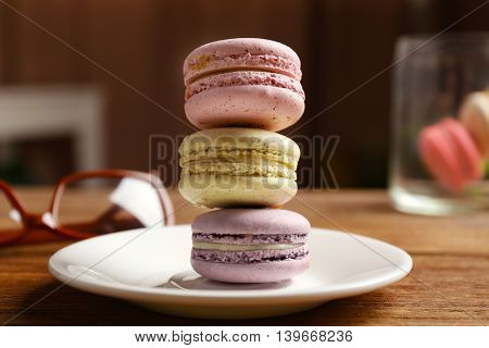 Tower of tasty macaroons in white plate on wooden table