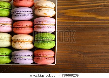 Different colorful macaroons in box on wooden background