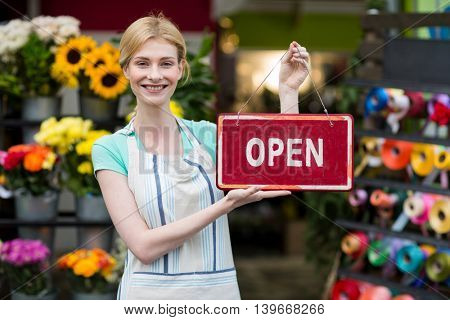 Female florist holding open signboard in the flower shop