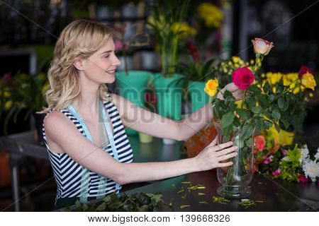 Smiling female florist arranging flower bouquet in vase at flower shop