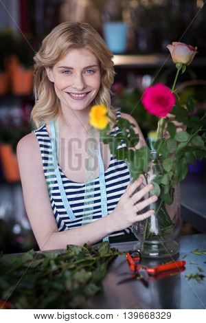 Portrait of smiling female florist arranging flower bouquet in vase at flower shop