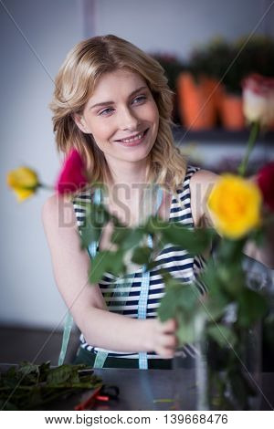 Smiling female florist arranging flower in flower shop