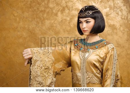 Thumbs down dislike gesture. Glamorous closeup portrait of beautiful sexy stylish brunette young woman model with bright makeup. Cleopatra