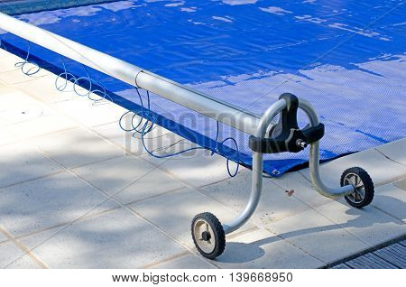 Swimming pool cover off its roller and covering the pool