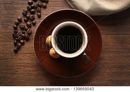 Cup of coffee with beans on wooden table