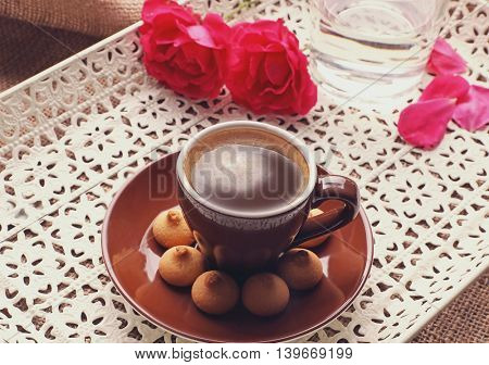 Cup of coffee with flower and cookies on tray