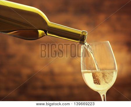 White wine pouring in glass on brown background