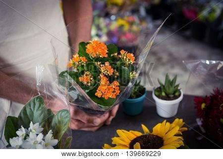 Close-Up of male florist holding bouquet of flower at his flower shop