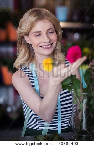 Smiling female florist arranging flower in vase at flower shop