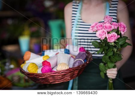 Mid-section of female florist holding bunch of flower in the shop