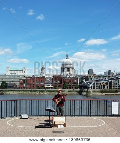 LONDON,UK - JULY 06, 2016: Street musician performs on Millennium Bridge near Tate Modern in London