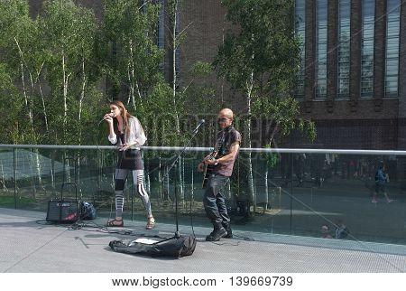 LONDON,UK - JULY 06, 2016: Two street musician perform on Millennium Bridge near Tate Modern in London
