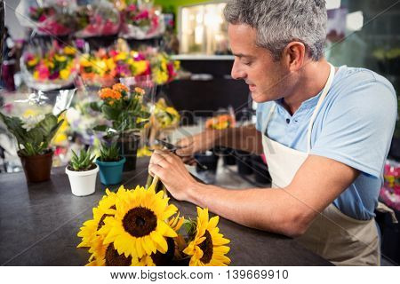 Close-Up of male florist trimming stems of flowers at his flower shop