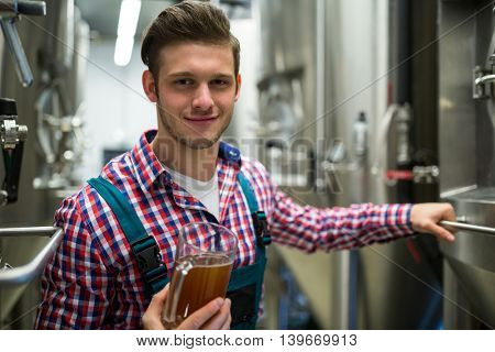 Brewer holding pint of beer at brewery factory