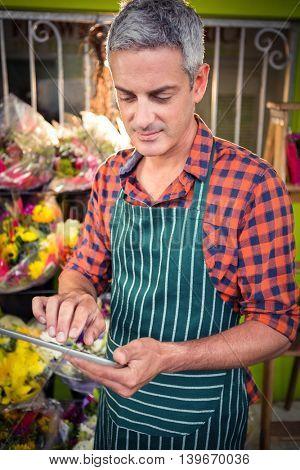 Male florist using digital tablet at his flower shop